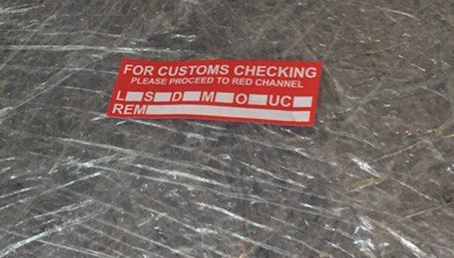 красные стикеры, которые клеят на багаж в Мале